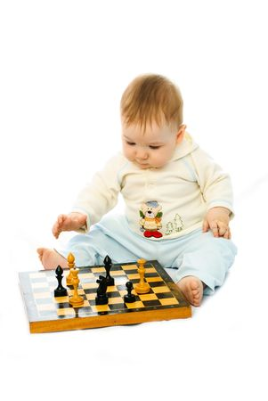 cute thoughtful ten months old baby playing chess on the floor photo