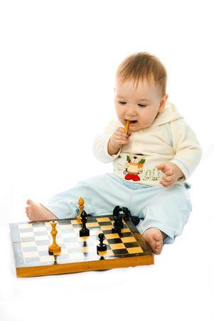 jugando ajedrez: lindo beb� de diez meses sentado en el suelo y jugando ajedrez Foto de archivo