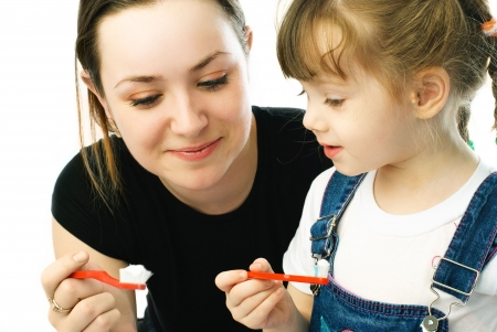 young beautiful mother teaching her little daughter brushing teeth Reklamní fotografie