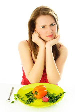 strong light: beautiful young woman keeping a diet and showing her disgust to vegetables Stock Photo