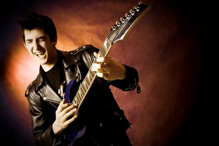 rockstar: studio portrait of a happy young excited man playing a guitar