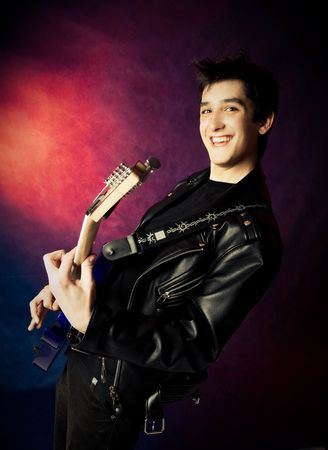 hardrock: studio portrait of a happy excited young man playing a guitar Stock Photo