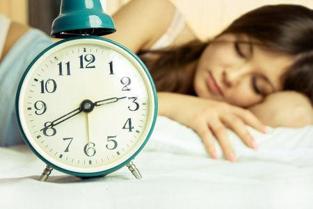 beautiful young brunette woman sleeping peacefully in bed with the alarm clock standing near her photo