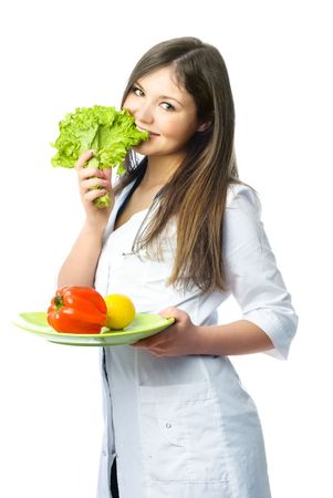 nutrition doctor: happy doctor dressed in white uniform holding a dish with vegetables and biting green salad
