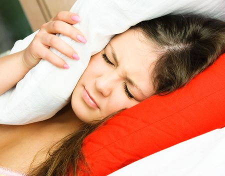 beautiful young woman suffering from insomnia and covering her head with a pillow Stock Photo - 4520375