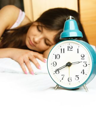 beautiful young woman sleeping peacefully in her bed with the alarm clock standing near her photo