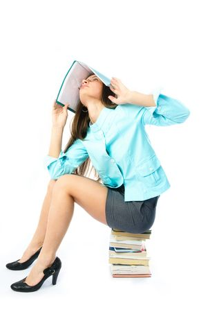 young beautiful student unwilling to do homework sitting on the books with a folder on her head  photo