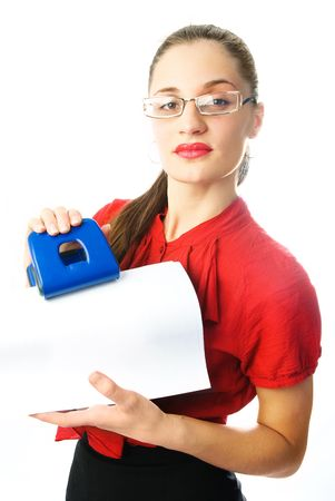 beautiful young businesswoman making holes in the sheet of paper with the help of a  Stock Photo - 4520070