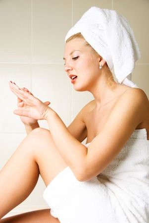 beautiful young woman pampering herself in the bathroom photo