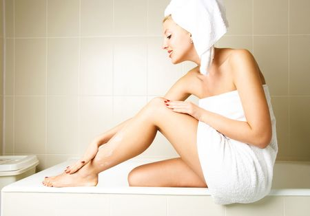 beautiful happy woman pampering herself and applying body lotion in the bathroom after the shower photo