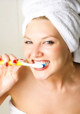 happy young beautiful woman brushing her teeth in the bathroom photo