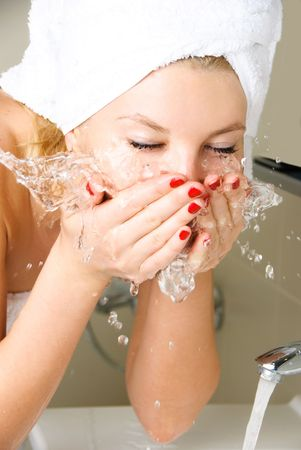 humidify: beautiful young woman washing her face in the bathroom