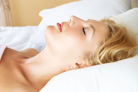 profile of a beautiful young blond woman sleeping peacefully in her bed at home photo