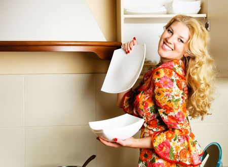 beautiful young laughing woman at home in the kitchen holding plates photo