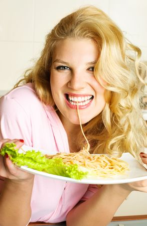 happy laughing beautiful woman at home in the kitchen eating spaghetti