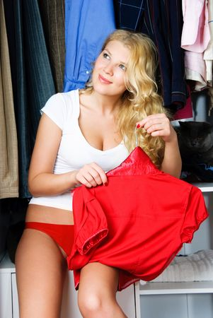 get dressed: portrait of a beautiful dreamy young woman sitting in the wardrobe and choosing what to put on Stock Photo