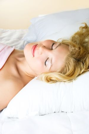 beautiful young blond woman sleeping in her bed at home photo