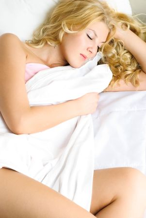 beautiful young blond woman sleeping peacefully in her bed at home photo