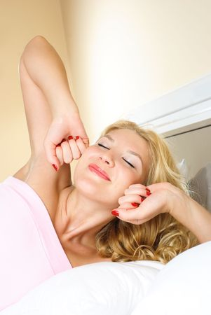 beautiful young blond woman at home in bed waking up and stretching