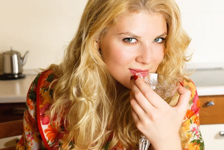 beautiful young woman drinking wine at home  in the kitchen photo