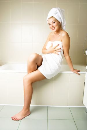 beautiful young woman wrapped into white towels in the bathroom photo