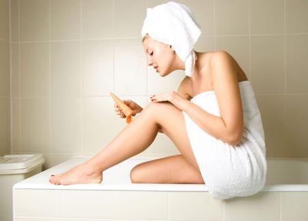 pampering: hermosa mujer feliz mimarse a s� misma en el cuarto de ba�o despu�s de la ducha y la aplicaci�n de una loci�n corporal Foto de archivo