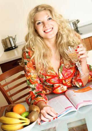 beautiful happy blond girl at home in the kitchen drinking wine and reading a magazine photo