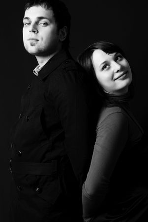 differ: black and white studio portrait of a serious man and a dreamy young woman standing back to back
