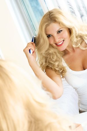 herself: pretty woman sitting at home by the mirror and brushing her hair