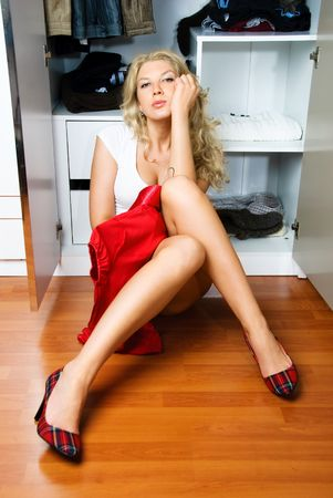 pretty blond woman sitting on the floor near the wardrobe and choosing what to put on Stock Photo