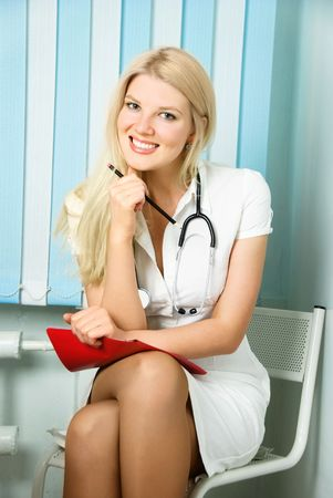 portrait of a beautiful young doctor with a stethoscope sitting by the table in her office  Stock Photo