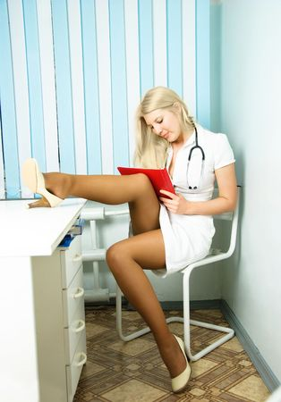 portrait of a sexy beautiful young doctor with a stethoscope sitting by the table in her office and writing