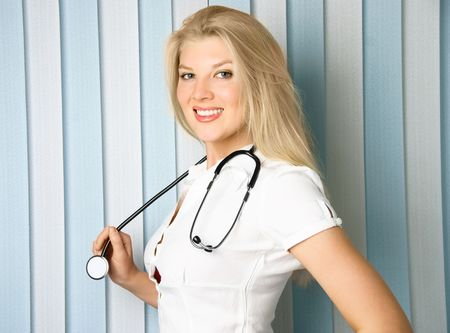 sexy female doctor: portrait of a young beautiful doctor with a stethoscope in the office