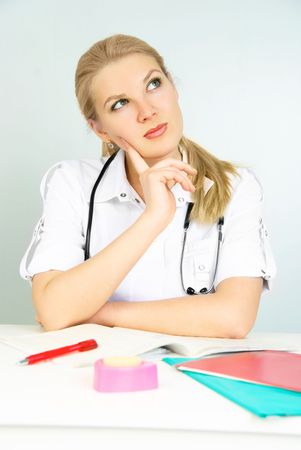 beautiful thoughtful young doctor sitting by the table in the office Stock Photo - 4694989