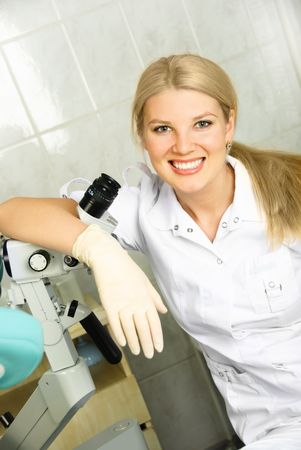 beautiful young gynecologist with a colposcope in her office