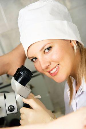 uniformes de oficina: ginec�logo examinar a un paciente en su oficina utilizando un colposcopio