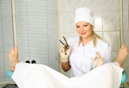 nurse gloves: portrait of a young gynecologist examining a patient in her office