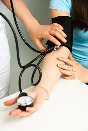 ipertensione: closeup delle mani di un medico di misurazione della pressione sanguigna di un paziente