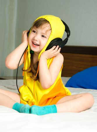 cute little girl sitting on the bed and listening to the music photo