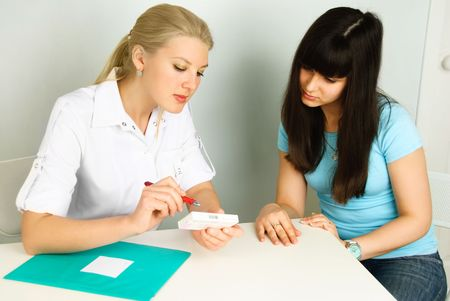 doctor sitting by the table and consulting a patient in her office Stock Photo - 4704065
