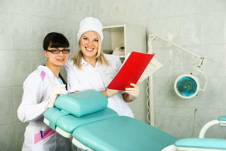 beautiful young doctor and ger assistant near the gynecological chair in the office Stock Photo - 4704062