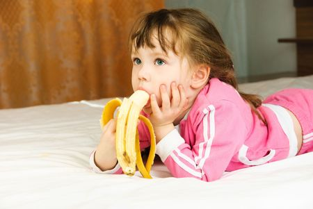 cute little girl eating a banana on the bed at home