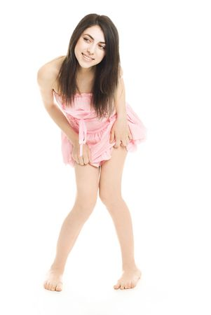 giggle: portrait of a pretty coquettish brunette girl wearing a pink dress