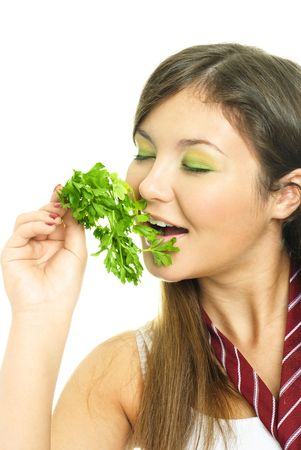 parsley digestion: portrait of a happy beautiful brunette girl eating fresh green parsley Stock Photo