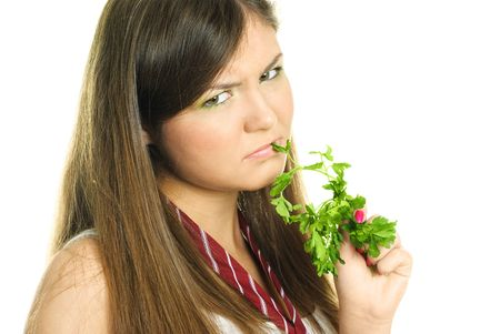 portrait of an unhappy beautiful brunette girl eating fresh green parsley photo