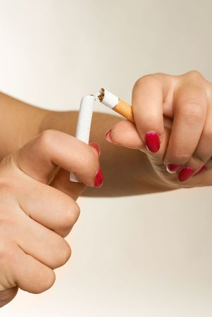demonstrative: closeup of the hands of a young woman breaking a cigarette  Stock Photo