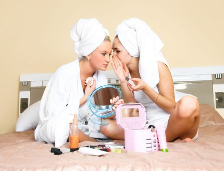 pamper: two pretty girls sitting on the bed at home and gossiping