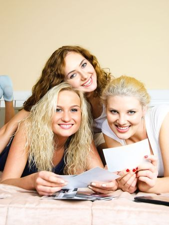 giggle: three happy friends lie on the bed and look through old photographs Stock Photo