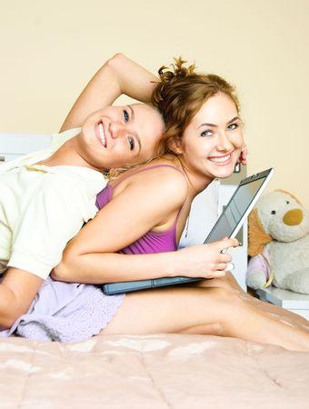 habladur�as: feliz retrato de dos estudiantes con un port�til en casa Foto de archivo