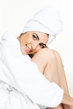 portrait of a pretty girl wrapped into the white towel and wearing a white dressing gown photo